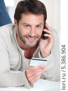 Улыбающийся мужчина с телефонной трубкой и банковской картой. Стоковое фото, фотограф Phovoir Images / Фотобанк Лори