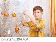 Купить «Мальчик наряжает серебристую елку дома», фото № 5394404, снято 15 декабря 2013 г. (c) Юлия Кузнецова / Фотобанк Лори