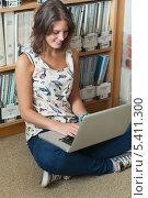 Smiling student against bookshelf using laptop on the library floor. Стоковое фото, агентство Wavebreak Media / Фотобанк Лори