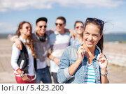Купить «девушка с наушниками на фоне своих друзей на природе», фото № 5423200, снято 20 июля 2013 г. (c) Syda Productions / Фотобанк Лори