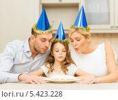 Купить «родители и дочь задувают свечи на торте», фото № 5423228, снято 26 октября 2013 г. (c) Syda Productions / Фотобанк Лори
