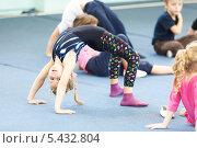 """Купить «Девочки делают """"мостик"""" на занятиях по акробатике», фото № 5432804, снято 21 декабря 2013 г. (c) Кекяляйнен Андрей / Фотобанк Лори"""