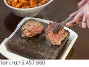 Купить «Steak sizzling on hot stone plate being sliced», фото № 5457660, снято 5 июня 2013 г. (c) Wavebreak Media / Фотобанк Лори
