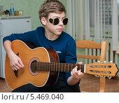 Купить «Мальчик-подросток в очках играет на гитаре», эксклюзивное фото № 5469040, снято 28 декабря 2013 г. (c) Игорь Низов / Фотобанк Лори