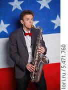 Купить «Молодой человек с саксофоном на фоне флага США», фото № 5471760, снято 11 января 2014 г. (c) Максим Топчий / Фотобанк Лори