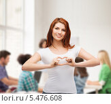 Купить «улыбающаяся девушка в аудитории сложила из пальцев сердце», фото № 5476608, снято 27 ноября 2013 г. (c) Syda Productions / Фотобанк Лори