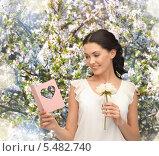 брюнетка на фоне цветущего сада читает открытку. Стоковое фото, фотограф Syda Productions / Фотобанк Лори