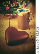 Шоколадное сердце на столе с чашечкой кофе и букетом цветом. Стоковое фото, фотограф Anhelina Tarasenko / Фотобанк Лори