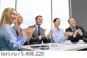 Купить «деловая команда за рабочим столом апплодирует невидимому коллеге», фото № 5498220, снято 9 ноября 2013 г. (c) Syda Productions / Фотобанк Лори