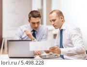 Купить «два бизнесмена обсуждают бумаги за рабочим столом», фото № 5498228, снято 9 ноября 2013 г. (c) Syda Productions / Фотобанк Лори