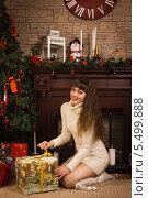 Купить «Девушка открывает подарок у новогодней елки на фоне камина», фото № 5499888, снято 9 декабря 2013 г. (c) Дмитрий Черевко / Фотобанк Лори