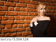 Красивая блондинка в черном вечернем платье на фоне кирпичной стены. Стоковое фото, фотограф Дмитрий Черевко / Фотобанк Лори