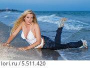 Купить «Привлекательная молодая длинноволосая блондинка лежит в одежде в набегающих морских волнах на песчаном пляже», фото № 5511420, снято 23 августа 2012 г. (c) Сергей Сухоруков / Фотобанк Лори