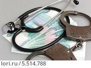 Купить «Стетоскоп, наручники и деньги на столе», фото № 5514788, снято 20 января 2014 г. (c) Алексей Карпов / Фотобанк Лори