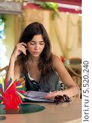 Купить «Одинокая девушка в ресторане изучает меню», фото № 5520240, снято 12 сентября 2012 г. (c) Михаил Иванов / Фотобанк Лори
