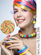 Купить «Девушка с сиреневыми ресницами и разноцветными ногтями держит леденец», фото № 5523396, снято 9 декабря 2013 г. (c) Типляшина Евгения / Фотобанк Лори