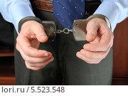Купить «Бизнесмен держит перед собой руки в наручниках», фото № 5523548, снято 21 января 2014 г. (c) Алексей Карпов / Фотобанк Лори