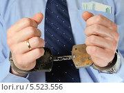 Купить «Бизнесмен держит перед собой руки в наручниках, в кармане рубашки лежат деньги», фото № 5523556, снято 21 января 2014 г. (c) Алексей Карпов / Фотобанк Лори