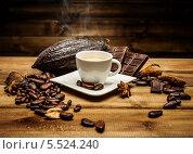 Купить «Чашка кофе на деревянном столе среди кофейных зерен и темный шоколад», фото № 5524240, снято 21 января 2014 г. (c) Andrejs Pidjass / Фотобанк Лори