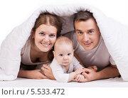 Купить «Молодая пара с маленьким ребенком лежит на постели под белым одеялом, на белом фоне», фото № 5533472, снято 29 января 2014 г. (c) Бандуренко Андрей / Фотобанк Лори