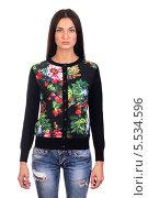 Купить «Молодая брюнетка в модной черной кофте с яркими цветами и рваных джинсах, изолированно на белом фоне», фото № 5534596, снято 29 октября 2013 г. (c) Egorius / Фотобанк Лори