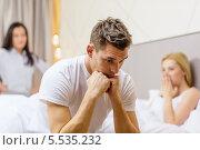 Купить «расстроенный мужчина сидит на постели на фоне двух расстроенных девушек», фото № 5535232, снято 23 ноября 2013 г. (c) Syda Productions / Фотобанк Лори