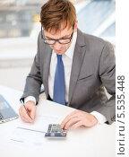 Купить «Бизнесмен в очках работает с бумагами, калькулятором и ноутбуком», фото № 5535448, снято 3 октября 2013 г. (c) Syda Productions / Фотобанк Лори