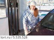 Купить «Девушка заправляет автомобиль на АЗС в зимнее время года», фото № 5535528, снято 19 января 2014 г. (c) Кекяляйнен Андрей / Фотобанк Лори