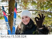 """Весёлая женщина брюнетка стоит с лыжами и показывает что всё будет """"окей!"""" (2014 год). Редакционное фото, фотограф Игорь Низов / Фотобанк Лори"""