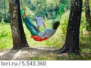 Купить «Молодая женщина в темных очках лежит в гамаке, натянутом между двумя толстыми березами, и читает книгу», фото № 5543360, снято 7 августа 2012 г. (c) Losevsky Pavel / Фотобанк Лори