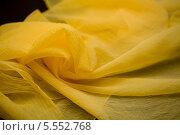 Купить «Желтая ткань на темном фоне», фото № 5552768, снято 14 августа 2013 г. (c) Morgenstjerne / Фотобанк Лори