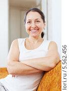 Купить «Улыбающаяся женщина в возрасте сидит на диване», фото № 5562456, снято 21 января 2013 г. (c) Яков Филимонов / Фотобанк Лори