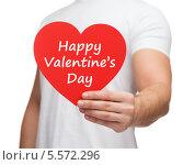 Купить «мужчина протягивает в камеру бумажное сердце с поздравлением с днем св. Валентина», фото № 5572296, снято 12 декабря 2013 г. (c) Syda Productions / Фотобанк Лори