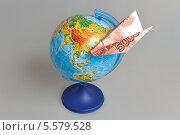 Купить «Самолетик из пятитысячной купюры и глобус», фото № 5579528, снято 9 февраля 2014 г. (c) Алексей Карпов / Фотобанк Лори