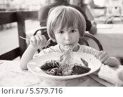 Купить «Мальчик ест пасту с морепродуктами в уличном кафе», фото № 5579716, снято 10 июля 2012 г. (c) Юлия Кузнецова / Фотобанк Лори