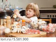 Купить «Маленькая девочка готовит на кухне», фото № 5581900, снято 29 сентября 2013 г. (c) Дарья Филимонова / Фотобанк Лори