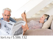 Couple with newspaper and cellphone in living room. Стоковое фото, агентство Wavebreak Media / Фотобанк Лори