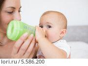 Купить «Mother feeding baby with milk bottle», фото № 5586200, снято 17 ноября 2013 г. (c) Wavebreak Media / Фотобанк Лори