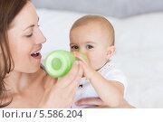 Купить «Mother feeding baby with milk bottle», фото № 5586204, снято 17 ноября 2013 г. (c) Wavebreak Media / Фотобанк Лори