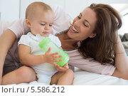 Купить «Mother with baby holding milk bottle on bed», фото № 5586212, снято 17 ноября 2013 г. (c) Wavebreak Media / Фотобанк Лори