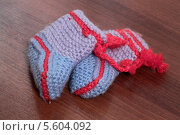 Купить «Детские вязанные пинетки на столе», фото № 5604092, снято 10 января 2014 г. (c) Данила Большаков / Фотобанк Лори