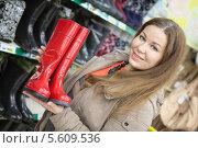 Купить «Довольный покупатель с красными резиновыми сапогами в руках стоит в магазине», фото № 5609536, снято 14 февраля 2014 г. (c) Кекяляйнен Андрей / Фотобанк Лори