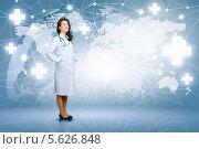 Купить «Очаровательная женщина-врач в белом халате на фоне карты мира стоит в полный рост и улыбается», фото № 5626848, снято 18 мая 2012 г. (c) Sergey Nivens / Фотобанк Лори