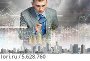 Купить «Серьезный бизнесмен смотрит в лупу на графики и диаграммы», фото № 5628760, снято 16 июня 2019 г. (c) Sergey Nivens / Фотобанк Лори