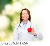 Купить «Сияющий врач в белом халате с красным сердцем», фото № 5641656, снято 20 декабря 2013 г. (c) Syda Productions / Фотобанк Лори