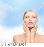Купить «Красивая девушка обняла лицо руками и смотрит вверх», фото № 5642004, снято 5 декабря 2013 г. (c) Syda Productions / Фотобанк Лори