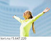 Купить «Спортивная девушка улыбается, раскинув руки на фоне небоскребов», фото № 5647220, снято 19 июня 2013 г. (c) Syda Productions / Фотобанк Лори