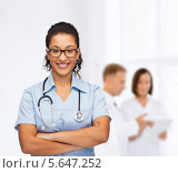 Купить «Молодой врач со фонендоскопом улыбается на фоне коллег», фото № 5647252, снято 12 декабря 2013 г. (c) Syda Productions / Фотобанк Лори