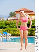 Купить «Молодая женщина делает гимнастику, стоя у бассейна», фото № 5649776, снято 10 июля 2012 г. (c) Losevsky Pavel / Фотобанк Лори