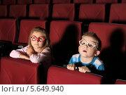 Купить «Мальчик и девочка с интересом смотрят фильм в кинотеатре», фото № 5649940, снято 20 ноября 2012 г. (c) Losevsky Pavel / Фотобанк Лори